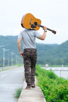 Guy with guitar standing on the dam