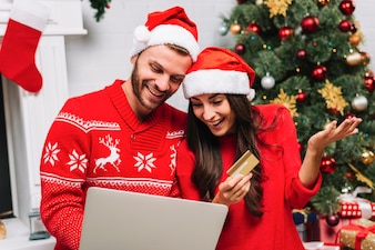 Guy with laptop near lady with credit card