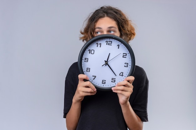 Guy with long hair in black t-shirt holding a wall clock on white wall