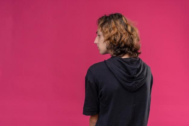 Ragazzo con i capelli lunghi in maglietta nera sta con la schiena sul muro rosa