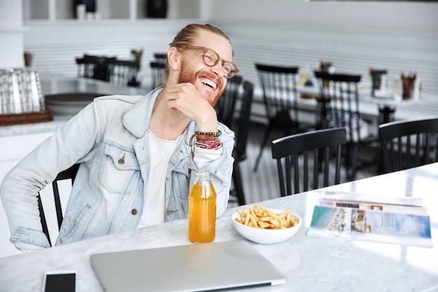 カフェでおしゃれなデニムジャケットを着た長い髪の男