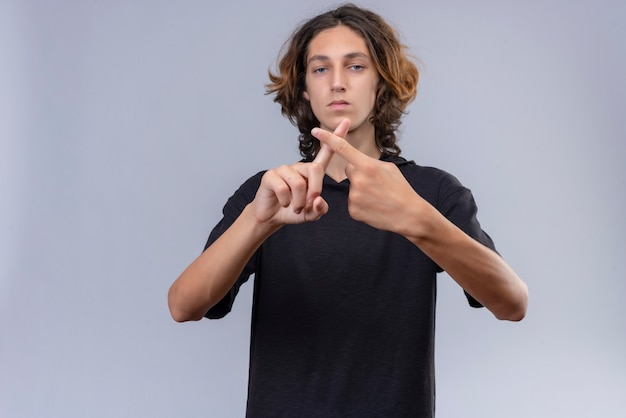 검은 티셔츠에 긴 머리를 가진 남자는 흰 벽에 손가락을 교차
