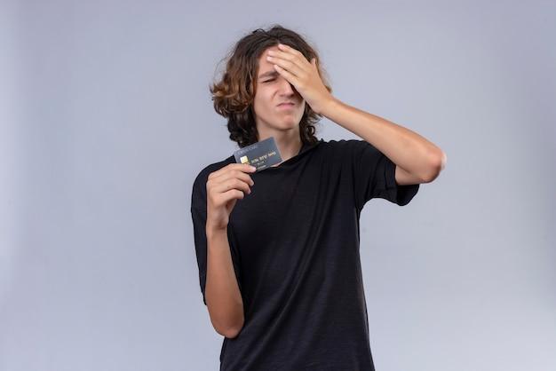 Парень с длинными волосами в черной футболке держит банковскую карту и схватился головой о белую стену