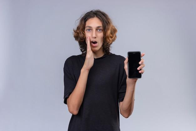 전화를 들고 흰 벽에 속삭이는 검은 티셔츠에 긴 머리를 가진 남자