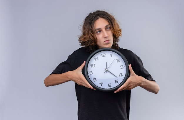 白い壁に壁時計を保持している黒いtシャツの長い髪の男