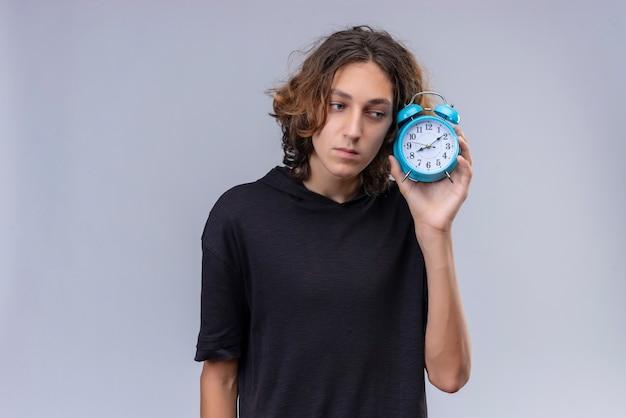 目覚まし時計を保持している黒いtシャツの長い髪の男
