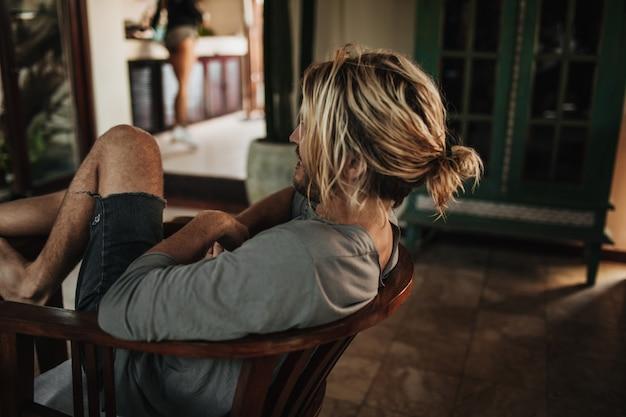 회색 셔츠와 찢어진 반바지에 긴 머리를 가진 남자는 나무 테이블에 다리를 두드리는 의자에 앉아 있습니다.