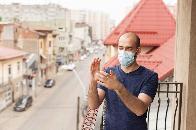 의료용 마스크를 쓴 남자는 코로나바이러스와 싸우는 의사들을 위해 연대에 박수를 보냅니다.