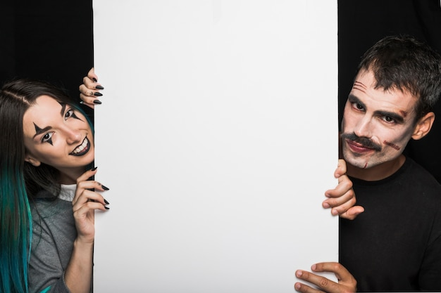 Guy with moustache and girl with azure hair holding tall white sheet