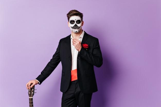 클래식 정장에 그려진 얼굴을 가진 남자는 기타에 기대어 거짓 콧수염으로 포즈를 취합니다.