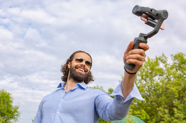 Guy with the phone on the stabilizer, he takes himself to the camera smartphone camera