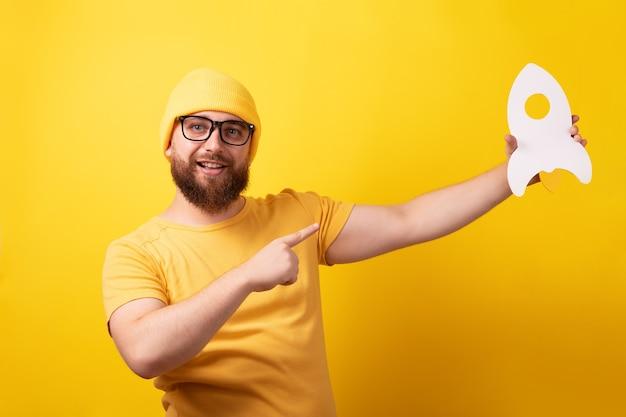 노란색 배경 위에 로켓을 든 남자, 시작 개념