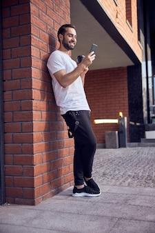 스마트 폰보고 커피를 마시는 미소를 가진 남자