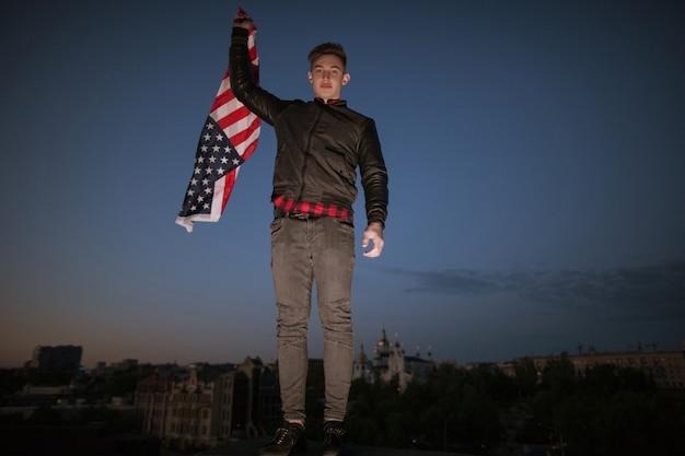 미국 밤 도시에서 깃발을 비행 남자. 자랑스러운 미국 애국자가 전국 행사를 축하합니다. 휴가 십대는 독립 기념일에 재미를