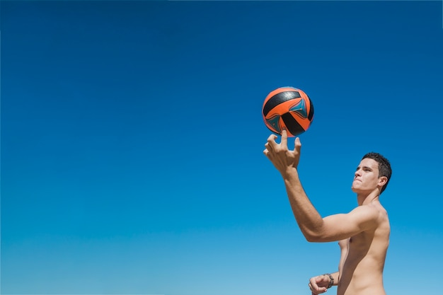 Guy with volleyball on finger