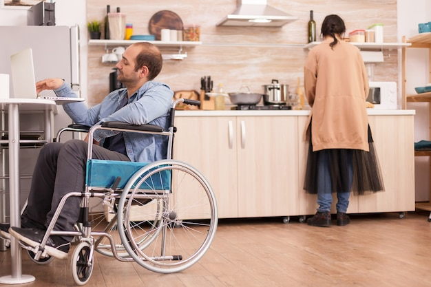 Guy with walking disability in wheelchair using laptop in kitchen and wife is cooking meal. disabled paralyzed handicapped man with walking disability integrating after an accident.