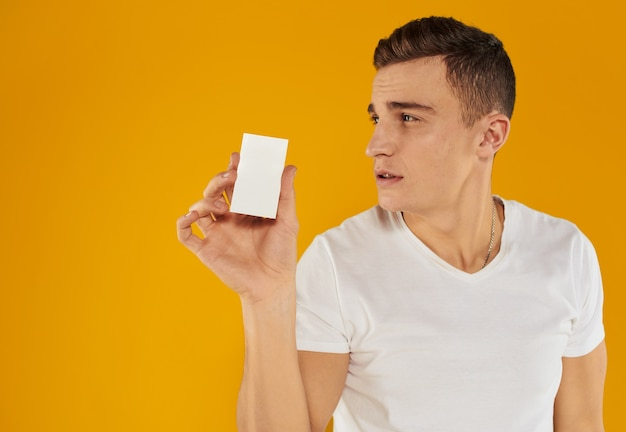 Guy with a white card on a yellow background copy space mockup