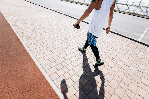 흰색 머리띠를 한 남자가 흰색 티셔츠, 검은색 레깅스, 파란색 반바지를 입고 화창한 날 외부의 보도를 따라 걷고 있습니다.