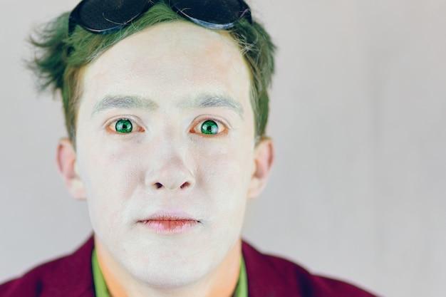 顔に白い化粧をし、スーツを着たピエロやパントマイムの俳優の緑の髪のグリースペイントをしている男は...