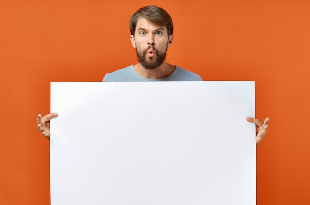Парень с белой бумагой на оранжевом фоне