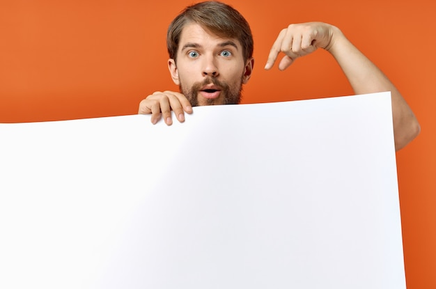 Guy with white paper on orange background poster mockup advertising sign. high quality photo