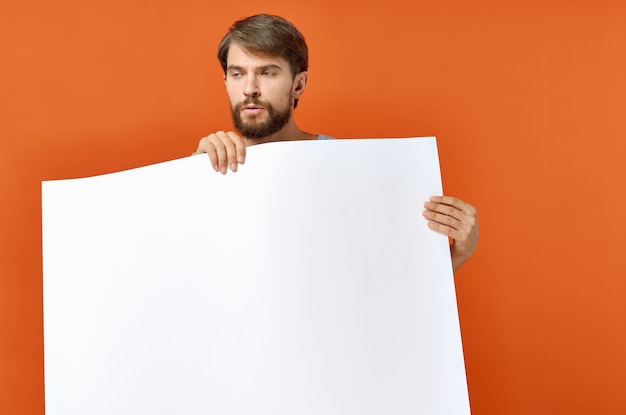 Guy with white paper on orange poster mockup advertising sign