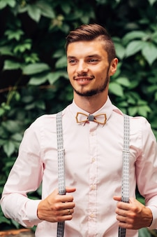Guy with wooden bow tie and suspenders smiles against the background of green leaves