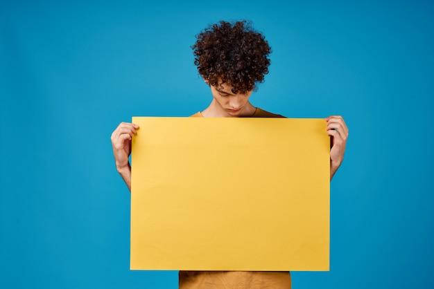 手に黄色のポスターを持つ男コピースペース広告青い背景