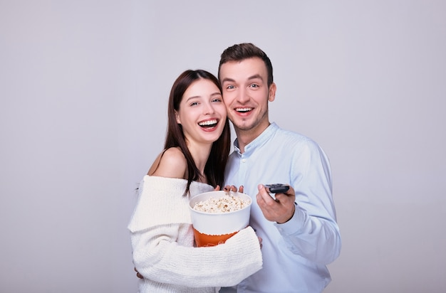 A guy and a woman with a tv remote control eat popcorn.