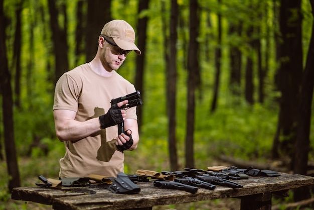 Guy in the woods tests his weapons for shooting sports