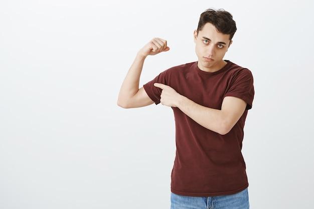Ragazzo che lavora ma ancora debole. ritratto del ragazzo bello dispiaciuto cupo in braccio di sollevamento della maglietta rossa e che mostra il bicipite