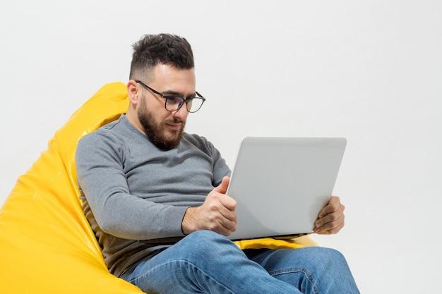Парень работает с ноутбуком, сидя на желтом пуф