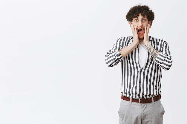 Ragazzo che urla vedendo un amico nudo. ritratto di shcoked e stordito bello maschio elegante con baffi e capelli ricci in camicia a righe che grida con le mani vicino alla bocca aperta in posa sopra il muro grigio