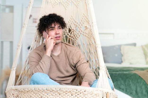가이 젊은 편안한 남자는 hamaca에 앉아 휴대 전화에 이야기