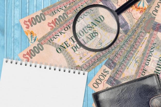 가이아나 달러 지폐와 검은 색 지갑과 메모장이있는 돋보기