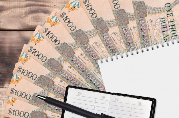 Вентилятор банкнот гайанских долларов и блокнот с контактной книгой и черной ручкой
