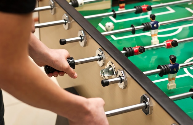 Guys are  playing table soccer indoor