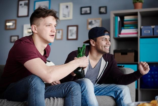 ビールを数杯飲んで応援している男たち