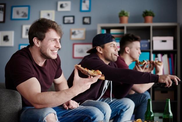 ジャンクフードを楽しんだり、テレビを見たりする男たち
