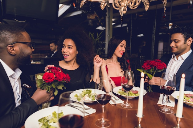 Guys give their girls roses in a restaurant.