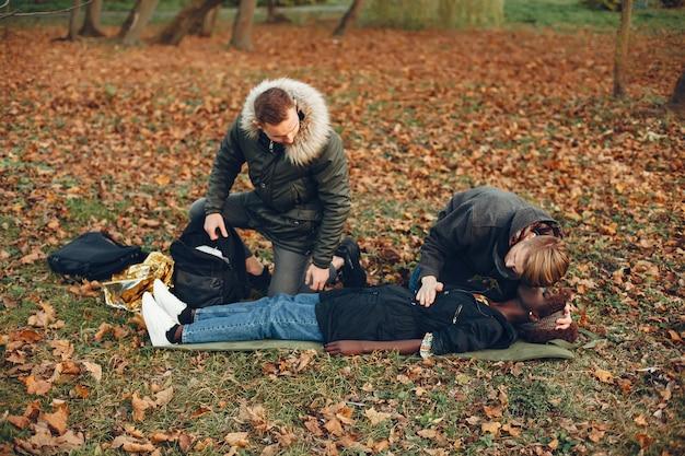 男は女性を助けます。アフリカの女の子は無意識に横たわっています。公園で応急処置を提供します。