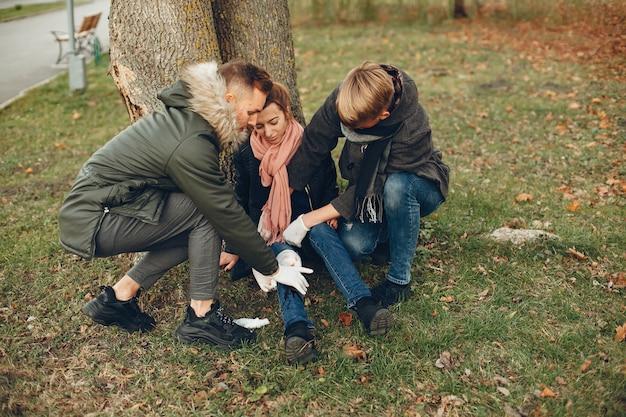 男は女性を助けます。足の骨折した少女。公園で応急処置を提供します。