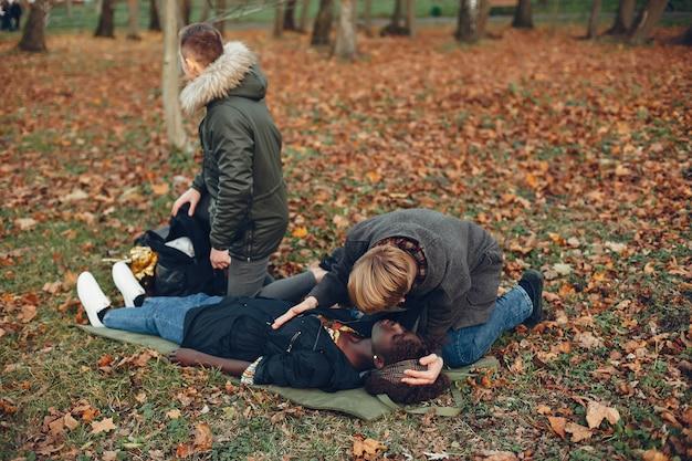 I ragazzi aiutano una donna. la ragazza africana sta mentendo inconscia. fornire il primo soccorso nel parco.