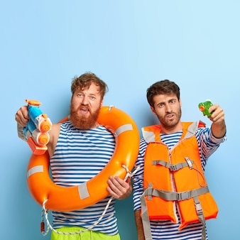 Guys posing at the beach with lifejacket and lifebuoy