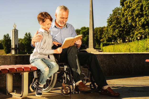 Guys read book together. rehabilitation outdoor.