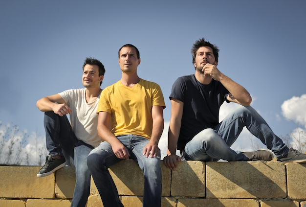 Guys sitting on a wall