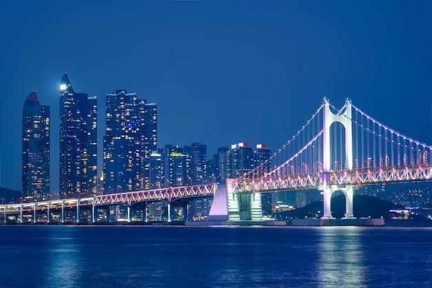 Мост гванган и небоскребы ночью. пусан, южная корея