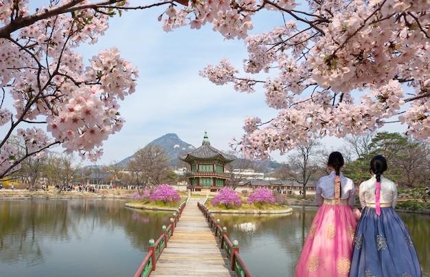 景福宮香遠亭パビリオン、韓国の国民服と春に桜が咲く、ソウル、韓国。