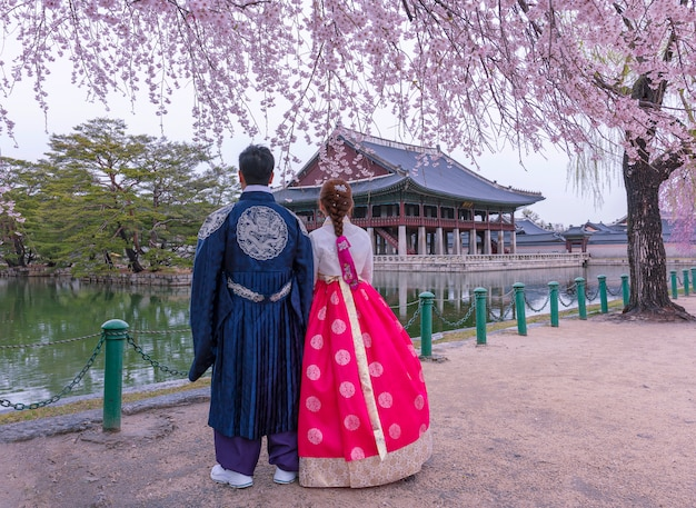 Дворец кёнбоккун с корейским национальным платьем и цветением вишни весной, сеул, южная корея.