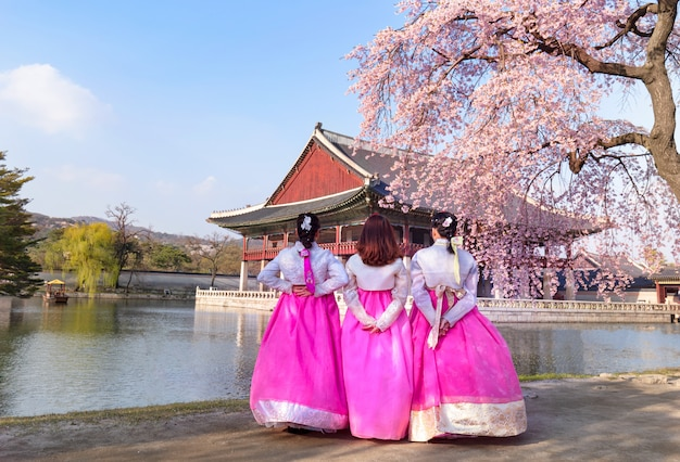 ソウル、韓国の春に韓国の民族衣装と桜の景福宮。
